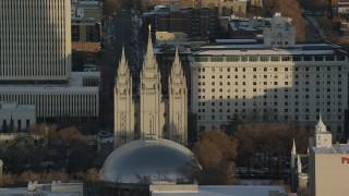 AX127_116 - 6K stock footage aerial video orbit of Salt Lake Temple at sunset with wintertime snow, Salt Lake City, Utah