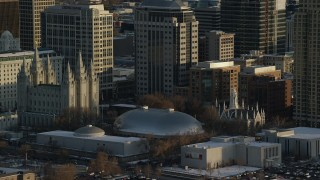 AX127_119 - 6K stock footage aerial video orbit Salt Lake Temple, Tabernacle and Assembly Hall at sunset with winter snow, Salt Lake City, Utah