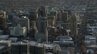 AX127_122 - 6K stock footage aerial video of Salt Lake Temple and Tabernacle in downtown with winter snow at sunset, Utah