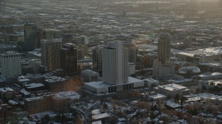 AX127_124 - 6K stock footage aerial video orbit tall buildings by Salt Lake Temple in downtown at sunset with winter snow, Utah