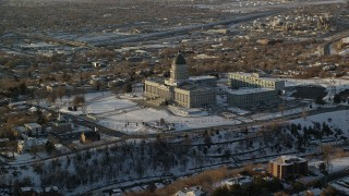 AX127_125 - 6K stock footage aerial video reverse view of the Utah State Capitol at sunset with winter snow, Salt Lake City