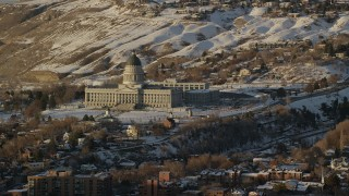 AX127_127 - 6K stock footage aerial video reverse view of the Utah State Capitol at sunset with winter snow on the ground, Salt Lake City