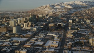 AX127_130 - 6K stock footage aerial video reverse view of streets through Downtown Salt Lake City to Utah State Capitol at sunset with winter snow