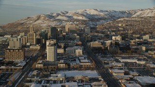 AX127_135 - 6K stock footage aerial video approach State Street through Downtown Salt Lake City at sunset with winter snow, Utah