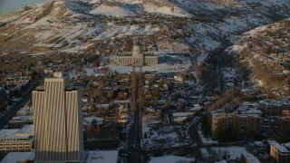 AX127_139 - 6K stock footage aerial video fly over State Street toward Utah State Capitol with winter snow at sunset, Salt Lake City