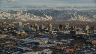 AX127_146 - 6K stock footage aerial video slow orbit of Downtown Salt Lake City with distant snow mountains at sunset, Utah