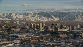 AX127_147 - 6K stock footage aerial video of orbiting Downtown Salt Lake City with distant snow mountains at sunset in wintertime, Utah