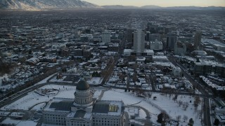 AX127_164 - 6K stock footage aerial video orbit back of Utah State Capitol with view of Downtown Salt Lake City with snow at sunset