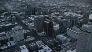 AX127_166 - 6K stock footage aerial video orbit office buildings in Downtown Salt Lake City at sunset with winter snow, Utah