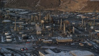 AX127_168 - 6K stock footage aerial video orbit of the Tesoro Refinery with winter snow at sunset, Salt Lake City, Utah