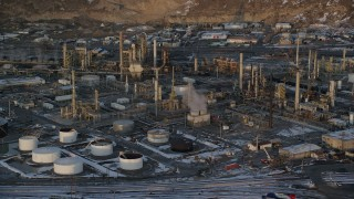 AX127_169 - 6K stock footage aerial video of circling the Tesoro Refinery in Salt Lake City with winter snow at sunset, Utah