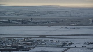 AX127_170 - 6K stock footage aerial video orbit SLC Airport with winter snow as an airliner races by at sunset, Utah
