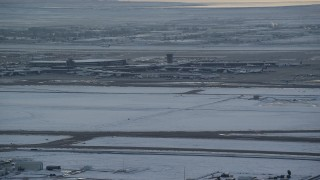 AX127_171 - 6K stock footage aerial video orbit airport runway as airliner lifts off in background at sunset with winter snow, Salt Lake City, Utah