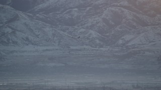 AX127_172 - 6K stock footage aerial video of tracking a commercial airline gaining altitude at sunset in winter, Salt Lake City, Utah
