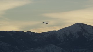 AX127_173 - 6K stock footage aerial video of tracking an airliner soaring over snow mountains at sunset in winter, Salt Lake City, Utah
