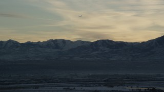 AX127_174 - 6K stock footage aerial video track commercial jet over snowy mountains by Salt Lake City at sunset in winter, Utah