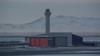 AX127_175 - 6K stock footage aerial video orbit Delta Hangar and airport control tower with winter snow at sunset, Salt Lake City, Utah