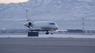 AX128_001 - 6K stock footage aerial video of tracking taxiing civilian jet at SLC Airport with winter snow at sunset, Utah