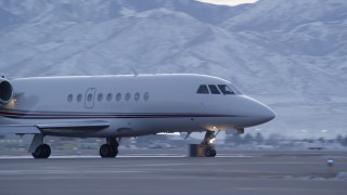 AX128_002 - 6K stock footage aerial video of tracking a passing private jet at SLC Airport with winter snow at sunset, Utah