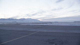 AX128_003 - 6K stock footage aerial video of low altitude approach to taxiways and winter snow at SLC Airport at sunset, Utah