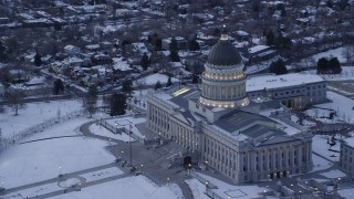 AX128_009 - 6K stock footage aerial video of orbiting the Utah State Capitol with flag flying and winter snow at twilight, Salt Lake City