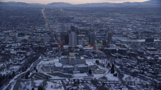 AX128_016 - 6K stock footage aerial video approach north side of Utah State Capitol and Downtown SLC with winter snow at twilight