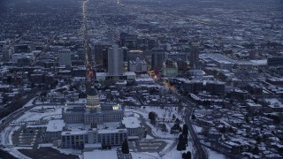 AX128_017 - 6K stock footage aerial video approach north side of state capitol and Downtown SLC with snow at twilight, Utah