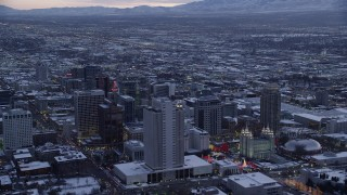 AX128_019 - 6K stock footage aerial video orbit Church Office Building and temple in Downtown Salt Lake City with winter snow at twilight, Utah