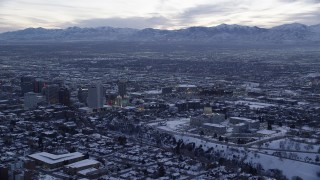 AX128_020 - 6K stock footage aerial video of a wide orbit of state capitol and Downtown Salt Lake City with winter snow at twilight, Utah
