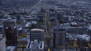 AX128_025 - 6K stock footage aerial video of following Main Street over office buildings in Downtown Salt Lake City, Utah in winter at twilight