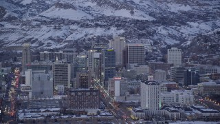 AX128_033 - 6K stock footage aerial video of Main Street and Downtown Salt Lake City, Utah buildings with winter snow at twilight