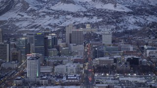 AX128_034 - 6K stock footage aerial video of passing State Street through Downtown Salt Lake City to capitol building with winter snow at twilight, Utah