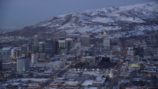 AX128_037 - 6K stock footage aerial video orbit State Street in Downtown Salt Lake City, with view of the capitol and winter snow at twilight, Utah