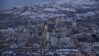 AX128_038 - 6K stock footage aerial video orbit State, Main and West Temple Streets through Downtown Salt Lake City, to Utah capitol with snow at twilight