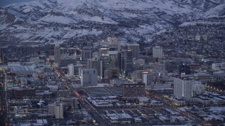 AX128_039 - 6K stock footage aerial video orbit Downtown Salt Lake City with winter snow seen from West Temple Street at twilight, Utah