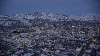 AX128_044 - 6K stock footage aerial video of a wide orbit of Downtown Salt Lake City seen from The Gateway in winter at twilight