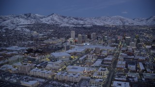 AX128_045 - 6K stock footage aerial video of the Gateway, arena, convention center and Downtown Salt Lake City with winter snow at twilight, Utah