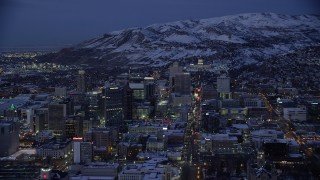 AX128_062 - 6K stock footage aerial video orbit Downtown Salt Lake City and State Street to the capitol with winter snow at Night, Utah
