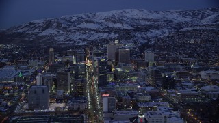 AX128_063 - 6K stock footage aerial video orbit from Main to West Temple Street in Downtown Salt Lake City with winter snow at night, Utah