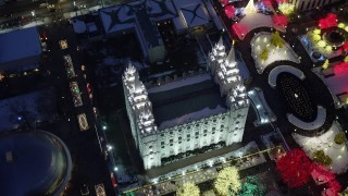 AX128_082 - 6K stock footage aerial video bird's eye orbit of Salt Lake Temple with Christmas lights and snow at night, Downtown Salt Lake City, Utah