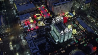 AX128_083 - 6K stock footage aerial video orbit Salt Lake Temple with snow and Christmas lights at night, Downtown Salt Lake City, Utah
