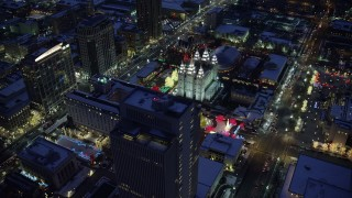 AX128_085 - 6K stock footage aerial video orbit Church Building by Salt Lake Temple lit for Christmas with winter snow at night, Downtown SLC, Utah