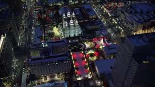 AX128_086 - 6K stock footage aerial video orbit fountains and Christmas lights at Salt Lake Temple with winter snow at night, Downtown Salt Lake City, Utah