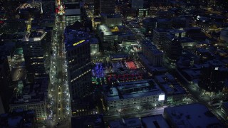 AX128_091 - 6K stock footage aerial video orbit Wells Fargo Building to reveal Gallivan Center with winter snow at night, Downtown Salt Lake City, Utah