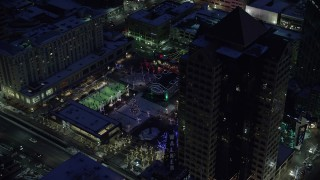 AX128_095 - 6K stock footage aerial video orbit office buildings and Gallivan Center, lit for Christmas in winter at night. Downtown SLC, Utah
