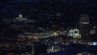 AX128_104 - 6K stock footage aerial video orbit capitol building, conference center, zoom in on Salt Lake Temple in winter, night, Downtown SLC, Utah