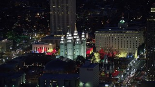AX128_105 - 6K stock footage aerial video orbit Salt Lake Temple with Christmas lights at night in wintertime, Downtown Salt Lake City, Utah