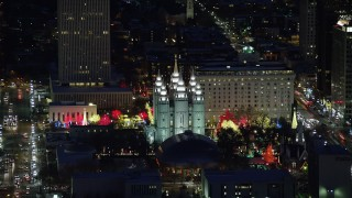 AX128_106 - 6K stock footage aerial video orbit Salt Lake Temple with bright Christmas lights at night in winter, Downtown Salt Lake City, Utah