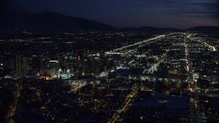 AX128_110 - 6K stock footage aerial video wide orbit of Salt Lake Temple and Downtown Salt Lake City, Utah at night in winter