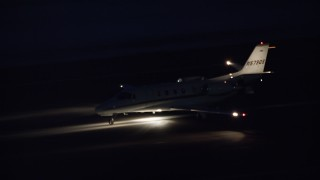 AX128_117 - 6K stock footage aerial video track private jet racing down runway at night in winter, Salt Lake City Airport, Utah